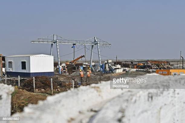 Workers labor at the project site for a 920squarekilometer industrial area located on the DelhiMumbai Industrial Corridor near the village of Dholera...