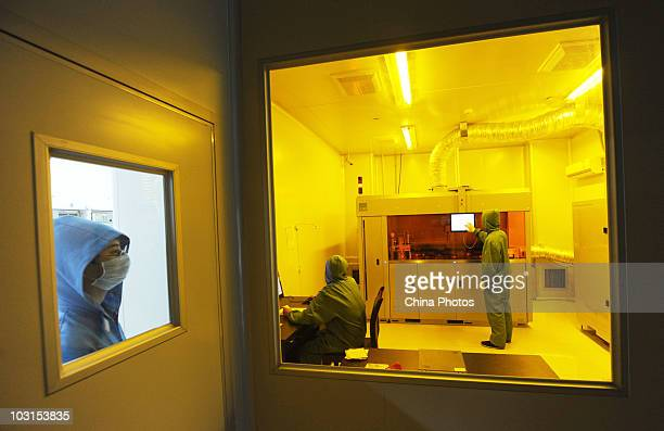 Workers labor in a master disc plant of the Yingshan Digital Technology Culture Development Company on July 29, 2010 in Shifang of Sichuan Province,...