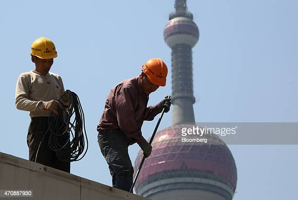 Workers labor in front of the Oriental Pearl Radio TV Tower at a construction site in the Lujiazui district of Shanghai China on Thursday April 23...