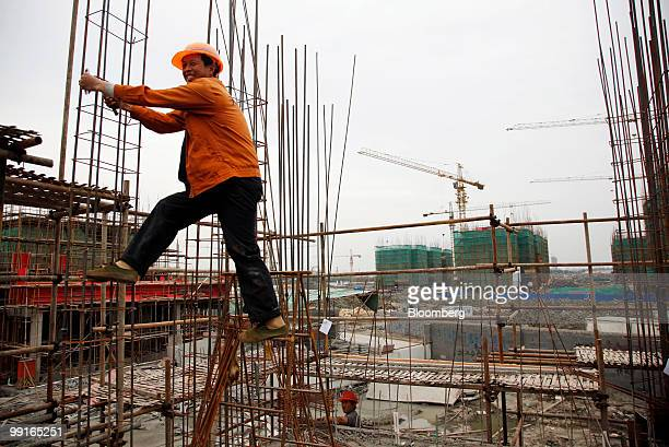 Workers labor on a construction site for a residential development in Shanghai China on Thursday May 13 2010 Shanghai's municipal government may levy...