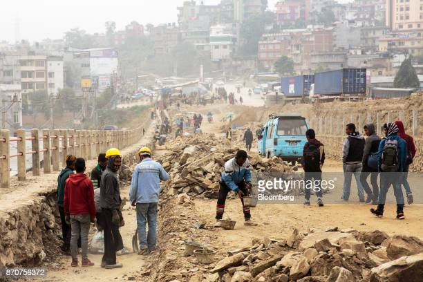 Workers labor on a construction site for a road operated by Shanghai Construction Group Co in the Kalanki Chowk area of Kathmandu Nepal on Wednesday...