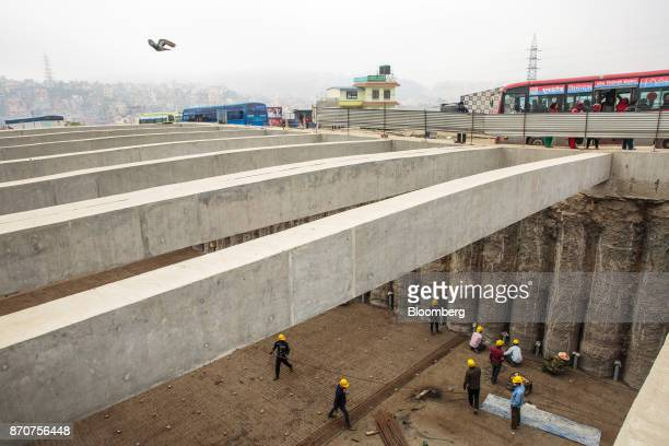 Workers labor on a construction site for an underpass operated by Shanghai Construction Group Co in the Kalanki Chowk district of Kathmandu Nepal on...