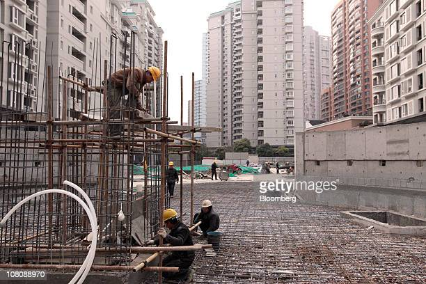 Workers labor on a construction site in Shanghai China on Monday Jan 17 2011 Shanghai China's financial center will this year prepare for a trial...