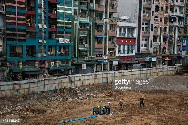 Workers labor on a construction site next to a row of residential buildings in Yangon Myanmar on Tuesday May 13 2014 Economic growth in Myanmar is...
