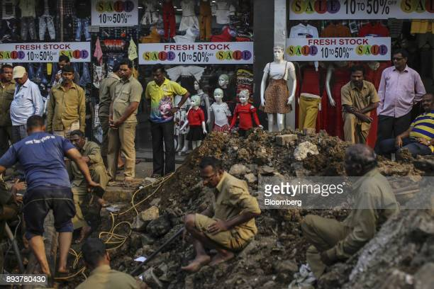 Workers labor on a road under construction in front of a clothing store in Mumbai India on Friday Dec 15 2017 India's inflation surged past the...