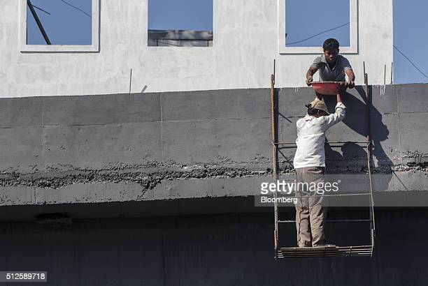 Workers labor on an overpass under construction in Chennai Tamil Nadu India on Thursday Feb 25 2016 India must review its fiscal deficit targets in...