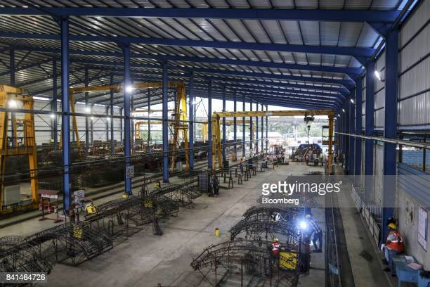 Workers labor on the steel reinforcing frames of precast concrete tunnel segments at the Mumbai Metro Rail Corp casting yard in Mumbai India on...