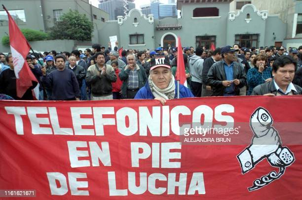Workers laid off by the Spanish Telephone Company holds up signs in front of the Embassy of Spain in Lima Peru 07 August 2002 Hundreds of...