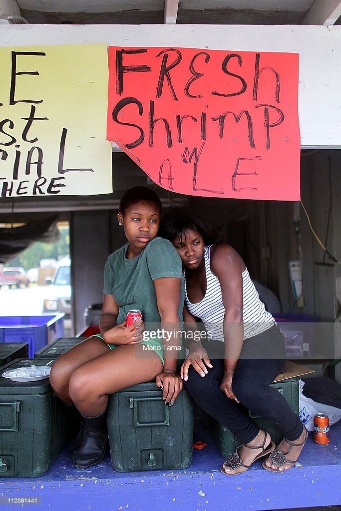 Workers La'Neka Ruffin (L) and Paris Scott sit on fish coolers at their stand at the Westwego seafood market April 19, 2011 in Westwego, Louisiana. The once thriving market, established in 1870, is struggling due to consumer concerns about the safety of local seafood. Ruffin says, 'A lot of customers came out before the oil spill but now they don't.'