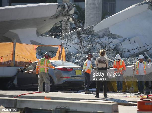 Workers law enforcement and members of the National Transportation Safety Board investigate the scene where a pedestrian bridge collapsed a few days...