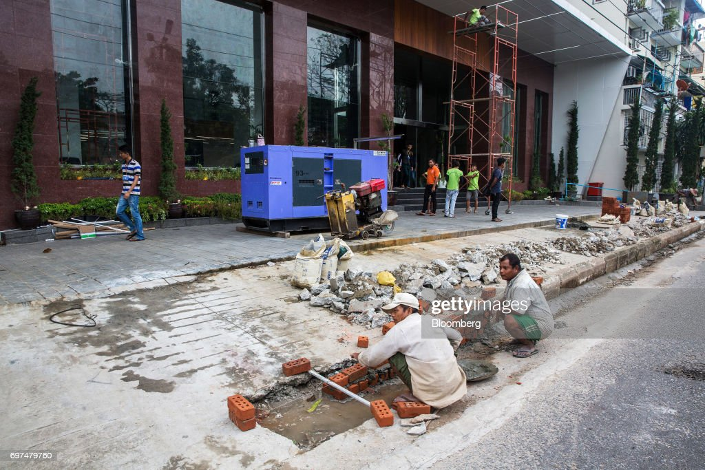 Workers lay bricks in front of the under construction Pan Pacific Yangon hotel, which will be operated by Pan Pacific Hotels Group, in Yangon, Myanmar, on Monday, June 12, 2017. When the country opened to the outside world in 2011 after decades of military rule, the former British colony held promise as one of the worlds hottest tourist destinations, a last frontier for adventure travel. But it hasn't worked out that way. A construction glut has flooded Myanmar with unused hotel rooms, and poorly regulated building has damaged national treasures like the archaeological site of Bagan. Photographer: Taylor Weidman/Bloomberg via Getty Images