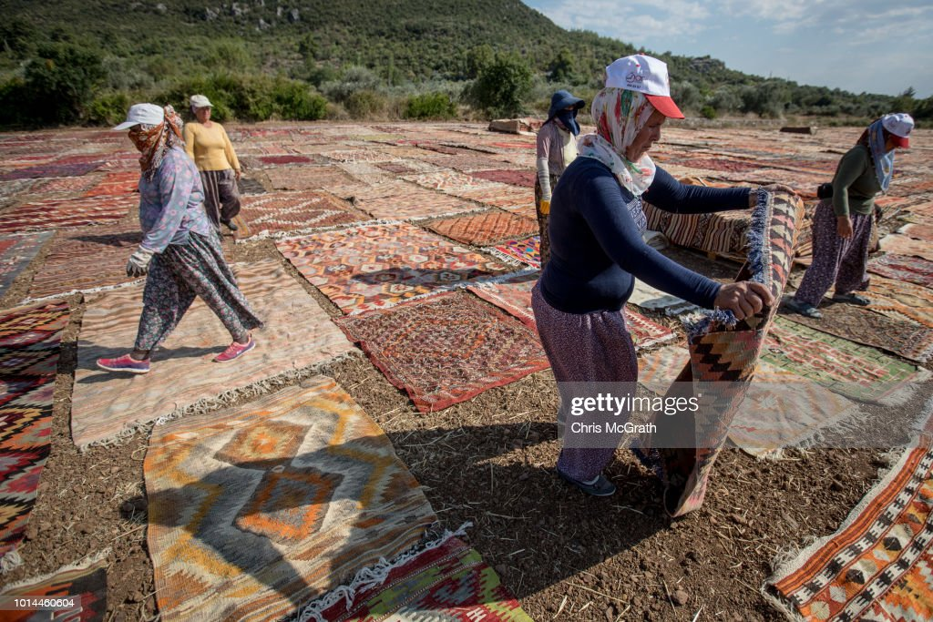 Workers lay carpets out to dry on August 10, 2018 in Dosemealti, Turkey. Turkey is famous for its artisan carpets but before they are sent to stores, masses of handmade carpets, flat woven kilims and embroidered rugs from all over Turkey are sent to the Dosemealti district in Antalya. The carpets are laid out in the sun and are turned regularly to soften the colors and give them an antique look. Turkey's carpet industry employs more than 40,000 people and exports have risen in the past five years to more than 10bn USD .