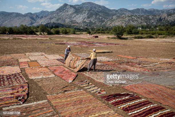 Workers lay carpets out to dry on August 10 2018 in Dosemealti Turkey Turkey is famous for its artisan carpets but before they are sent to stores...