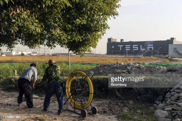 Workers lay fiber optic cables underground near the Tesla Inc Gigafactory in Shanghai China on Friday Nov 1 2019 After starting construction this...