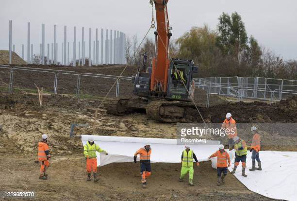 Workers lay out polythene sheeting as they prepare ground works at a site purchased by the UK government to use a customs clearance facility near...