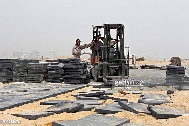 Workers lay paving slabs on reclaimed land at the Eko Atlantic city site, developed by Eko Atlantic, near Victoria island in Lagos, Nigeria, on...