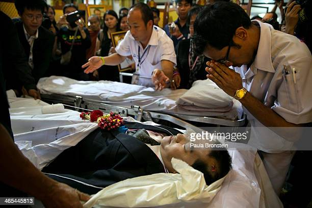 Workers lay the body of Sutin Tharatin a core antigovernment leader who was killed by gunmen yesterday in Bangkok on January 27 2014 in Bangkok...