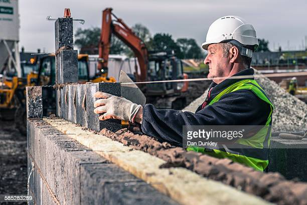 Workers laying bricks on construction site