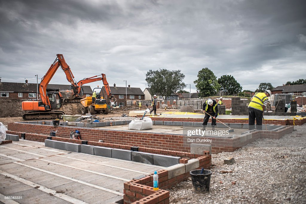Workers laying bricks on construction site : Stock Photo