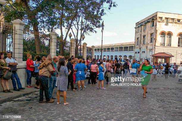 Workers leave the building of the Lonja del Comercio building after a quake in Havana on January 28, 2020. - A major 7.7 magnitude quake struck...