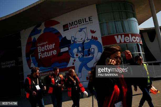 Workers leave the main hall of the Mobile World Congress on February 24 2018 ahead of the start of the world's biggest mobile fair held from February...