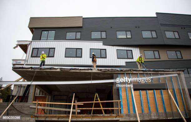 Workers lift a beam to install on the Josie Hotel under construction at the Red Mountain ski resort in Rossland British Columbia Canada on Wednesday...