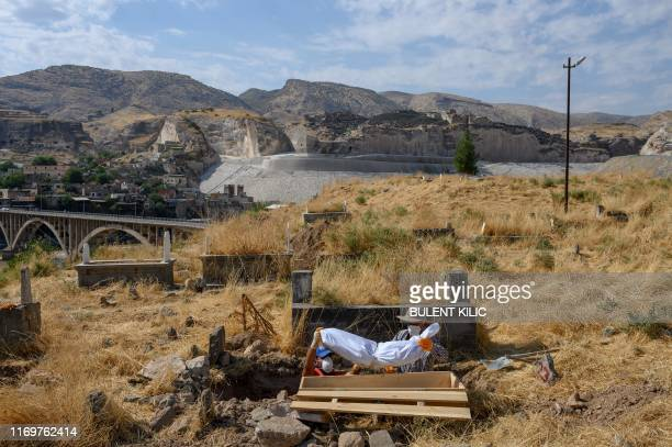 Workers lift a corpse from the old Hasankeyf cemetery to be moved to the new Hasankeyf cemetery on September 13 on the banks of the Tigris in...