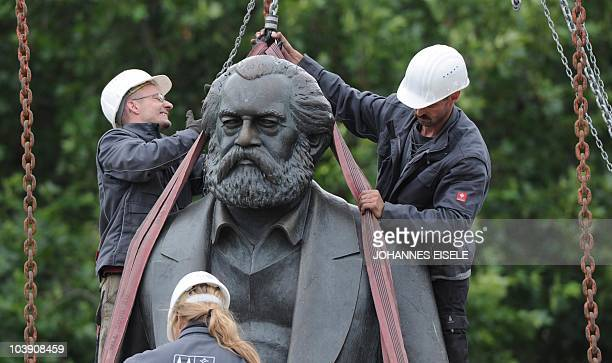 Workers lift a statue of German philosopher political economist and sociologist Karl Marx off its base in Berlin on September 8 2010 Two statues Marx...