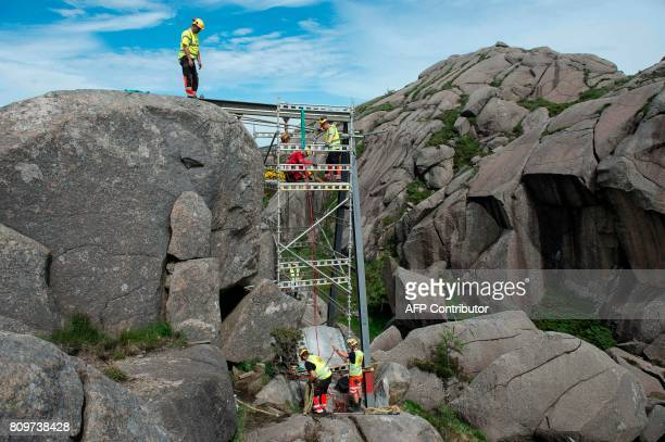 Workers lift in place the rock formation Trollpikken in Rogaland western Norway on July 6 2017 The rock formation was vandalized during the night on...