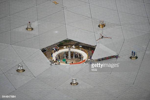Workers lift the last panel to install into the center of a Fivehundredmeter Aperture Spherical Telescope on July 3 China The dishlike telescope as...