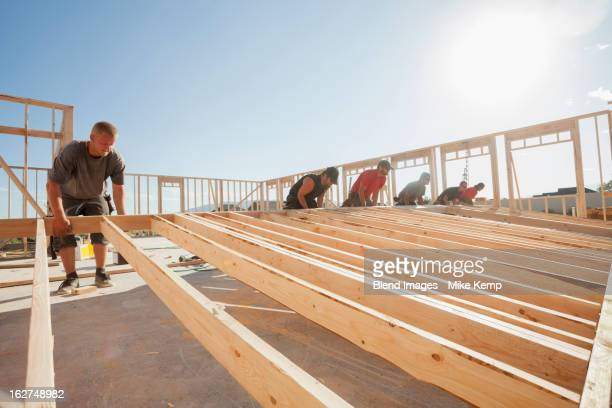 Workers lifting frame on construction site