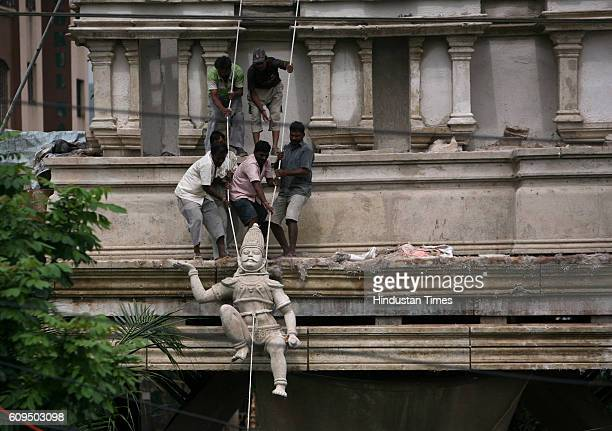 Workers lifting up an idol as they are sculpting a replica of the entire Tirupati temple in Thakur Complex Borivli for the Ganeshotsav