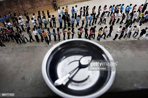 Workers line up to get lunch at the Shenzhen Quanshun Human Resources Co Ltd on February 26 2009 in Shenzhen Guangdong Province China The company...