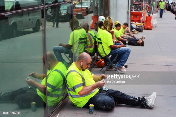 Workers lined up on a sidewalk. taking a lunch break in Midtown Manhattan, in NYC.