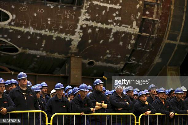 Workers listen as Britain's Defence Secretary Michael Fallon speaks after watching the first piece of steel for the successor submarine programme...