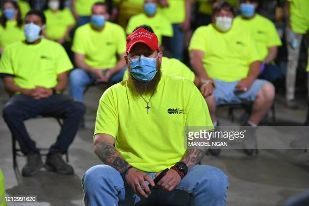 Workers listen as US President Donald Trump speaks during a visit to medical supply distributor Owens and Minor Inc. In Allentown, Pennsylvania on...