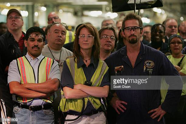 Workers listen to Alan Mulally, President and CEO of Ford Motor Company, and other VIPs speak at a ceremony celebrating the launch of the new Ford...