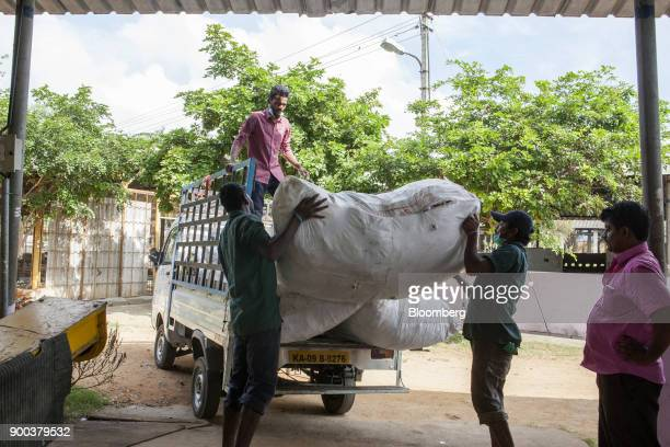 Workers load a bag of sorted dry household waste onto the back of a truck in a warehouse at a recycling facility operated by Mysuru City Corp in...