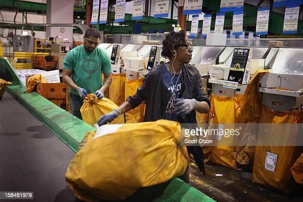 Workers load a bags of mail onto a conveyor at the United States Postal Service Chicago Logistics and Distribution Center on December 17 2012 in Elk...
