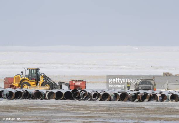 Workers load a truck with equipment at a pipe yard for the Keystone XL pipeline in Oyen, Alberta, Canada, on Tuesday, Jan. 26, 2021. U.S. President...