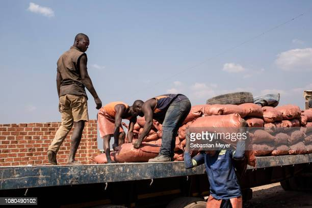 Workers load a truck with sacks of cobalt at the Musompo market on the outskirts of Kolwezi nnnCobalt is a vital mineral needed for the production of...