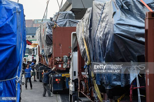 Workers load an impounded tarpaulincovered armoured troop carrier Terrex vehicle belonging to the Singapore military onto a truck at a customs and...