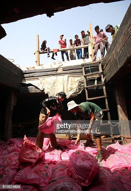 Workers load bags of dates aboard a shipping boat bound for Dubai and India on September 26 at Khor alZubair port near the southern Iraqi city of...