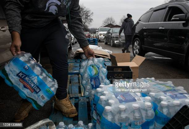 Workers load bottled water into vehicles waiting in line at a water distribution site at Greater Holy Temple in Flint, Mich., on Thursday, December...