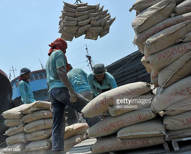 Workers load cement bags onto a ship for domestic distribution at Jakarta's traditional port of Sunda Kelapa in Jakarta on February 13 2013...