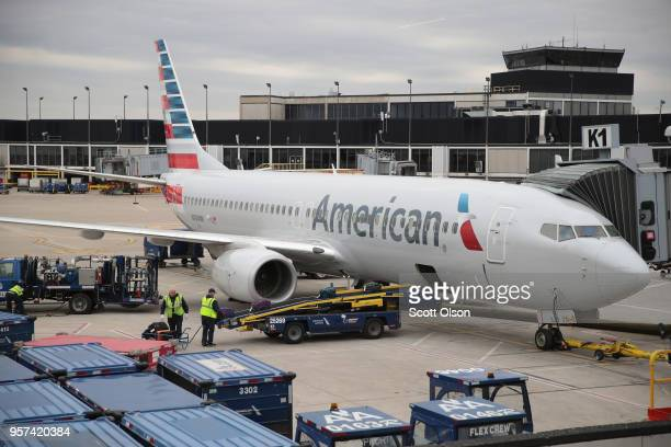 Workers load luggage onto an American Airlines aricraft at O'Hare International Airport on May 11 2018 in Chicago Illinois Today American Airlines...