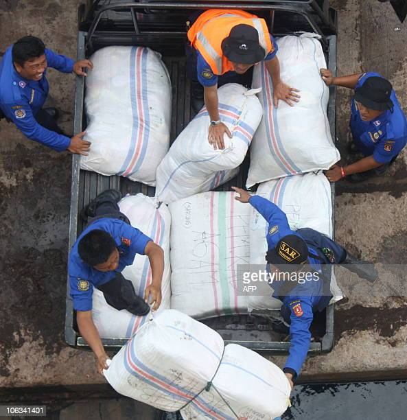 Workers load relief goods for tsunami victims in the Mentawai islands onto a supply ship at the port of Padang in West Sumatra on October 29 2010...
