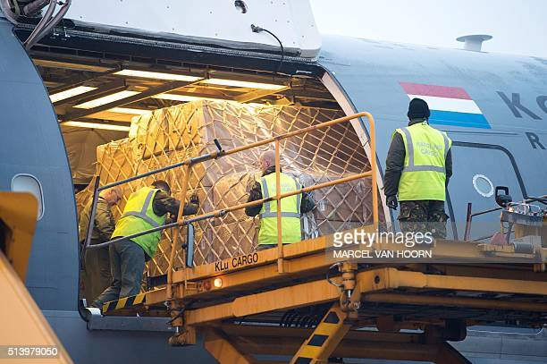 Workers load relief goods into a Dutch military cargo plane at Eindhoven airport on March 6 2016 The plane carrying blankets sleeping bags and camp...