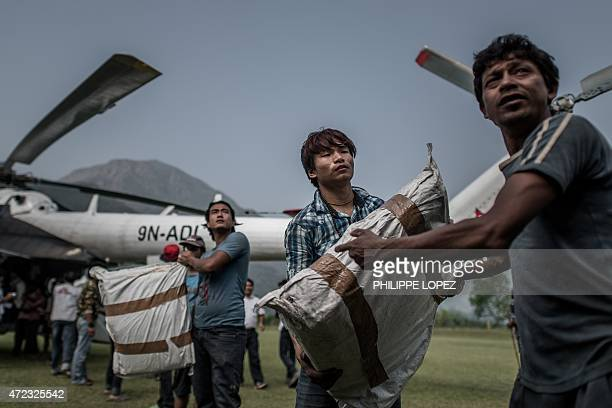 Workers load relief supplies in a helicopter for the World Food Programme in Deurali village of Nepal's Gorkha district on May 6 2015 The earthquake...