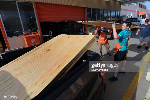 Workers load sheets of plywood into a customer's truck at a Home Depot store in preparation for the arrival of Hurricane Dorian which is expected to...
